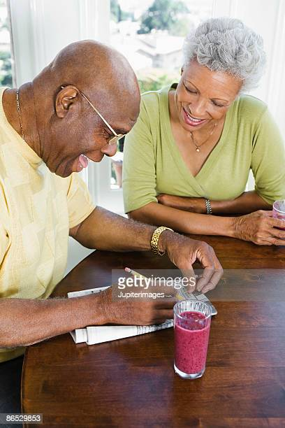 Couple doing crossword at table
