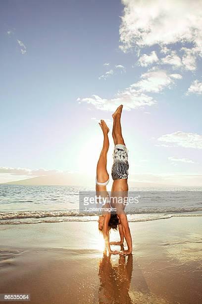 Couple doing handstands on beach