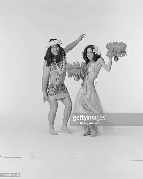 Couple doing hula dance, smiling, portrait