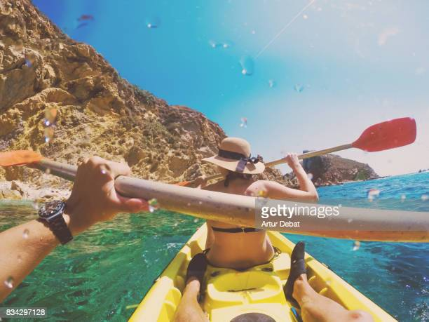 Couple doing kayak taking picture from boyfriend personal perspective exploring the natural Medes islands in the shoreline of Costa Brava Mediterranean Sea during summer vacations in a paradise place.