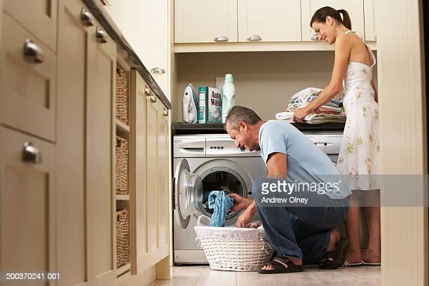 Couple doing laundry in kitchen, man loading washing machine