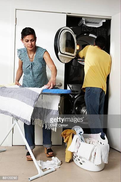 Couple faisant de blanchisserie dans la buanderie