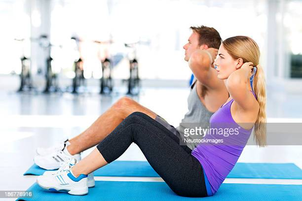 Couple Doing Sit-ups In Health Club