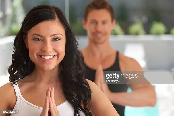 Couple doing yoga at a health club