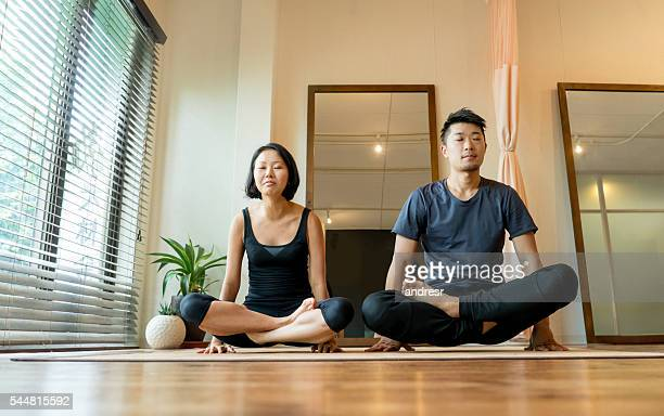 Couple doing yoga at home