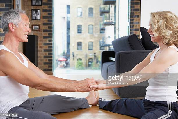 Couple doing yoga in living room