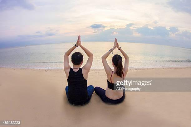 Couple doing yoga on the beach