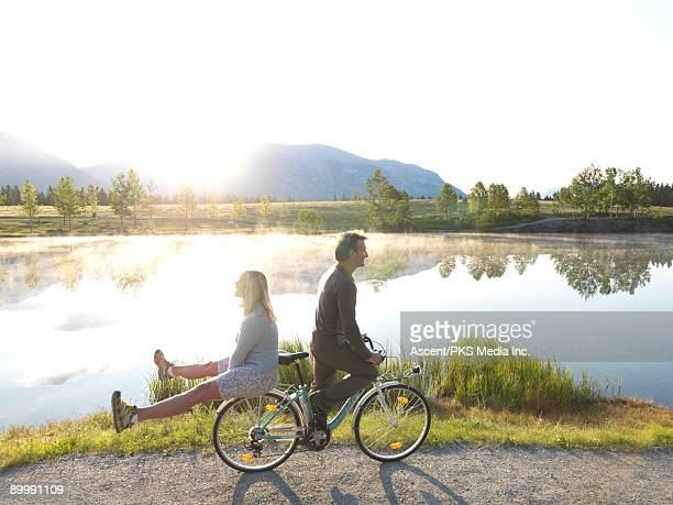 Couple double on bike at edge of mountain lake