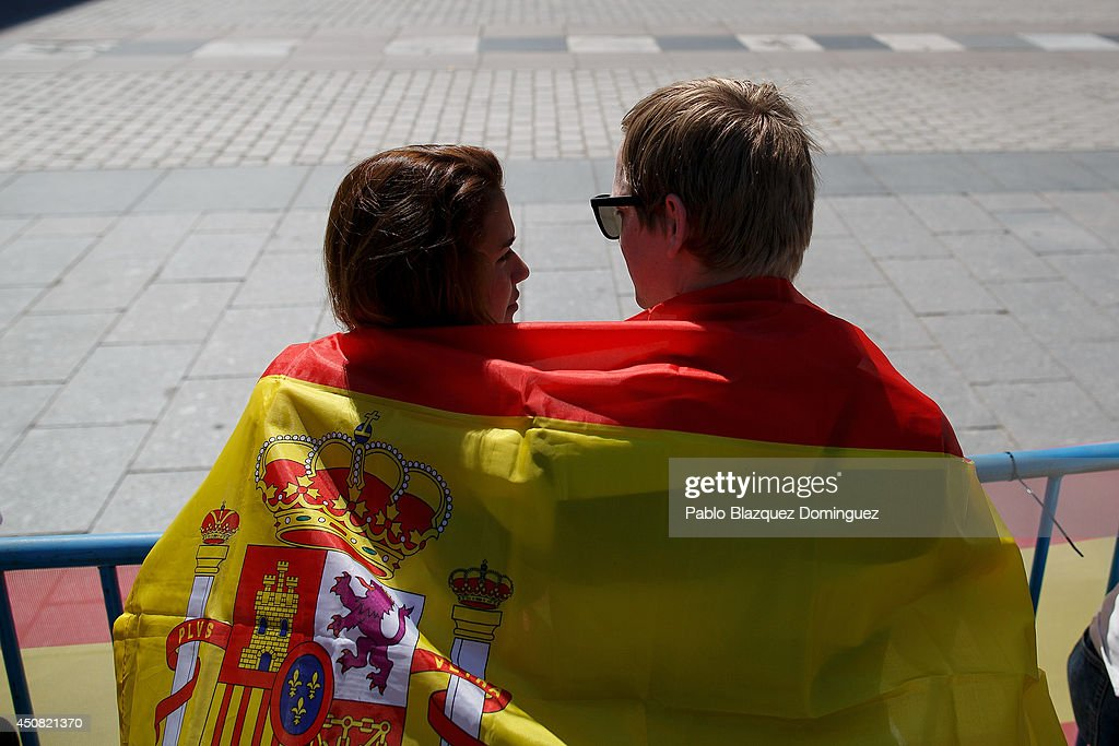 A couple drape a Spanish flag around them selves as they watch the Royal Guard parade outside the Royal Palace as King Juan Carlos prepares to sign the official abdication papers on June 18, 2014 in Madrid, Spain. Tomorrow Prince Felipe will be crowned Felipe VI of Spain on June 19th after his father King Juan Carlos abdicated.