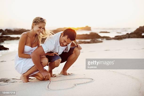 Paar zeichnen ein Herz-Form in den sand