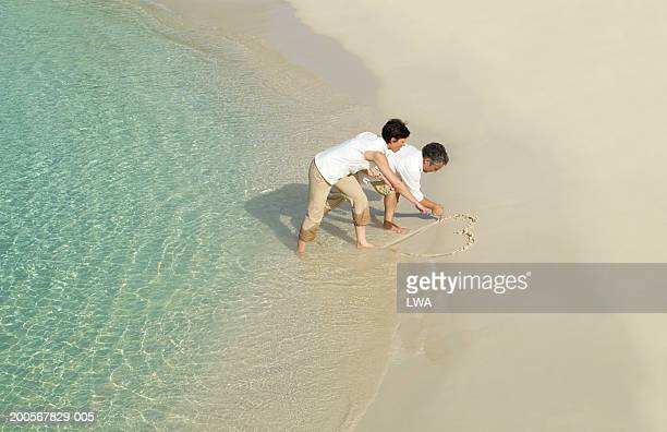 Couple drawing heart in sand on beach, elevated view