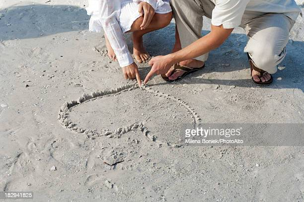 Couple drawing heart in sand on beach, loaw section