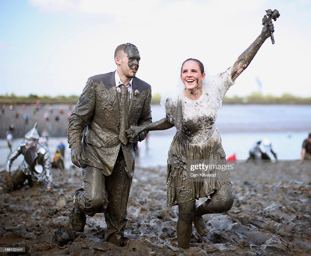 A couple dressed as a bride and groom take part in the Maldon Mud Race on May 05, 2013 in Maldon, Essex. The race originated in 1973 and involves competitors racing around a course on the mudbanks of the river Blackwater at low tide.