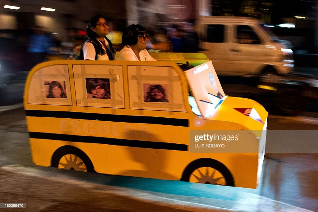 A couple dressed as a school bus riding their motorbike during 'Moto-Halloween Party 2013' on October 30, 2013, in Cali, Valle del Cauca department, Colombia. AFP PHOTO/Luis ROBAYO