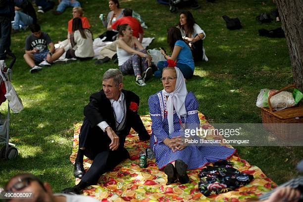 A couple dressed as 'Chulapos' sit on the grass during the San Isidro festivities at Pradera de San Isidro park on May 15 2014 in Madrid Spain During...
