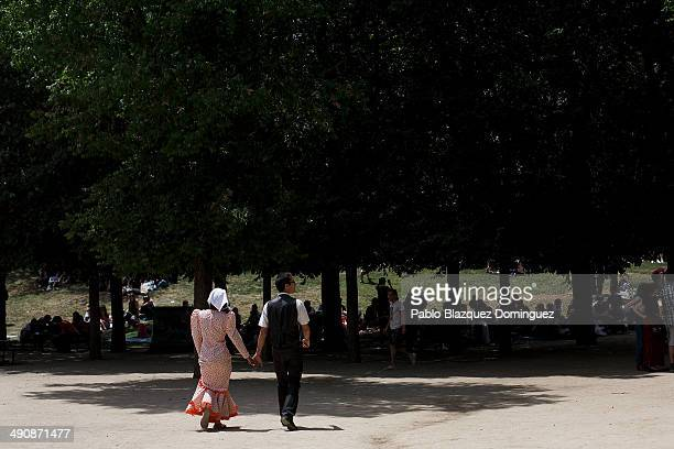 A couple dressed as 'chulapos' walk at Pradera de San Isidro park during the San Isidro festivities on May 15 2014 in Madrid Spain During the...