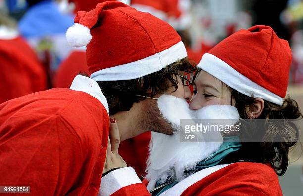 A couple dressed as Santa Claus kiss as they take part in a parade in downtown Porto December 20 2009 Thousands marched in an attempt to break the...