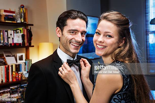 Couple dressed up, woman straightens bowtie of man