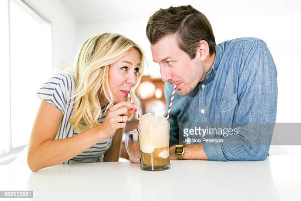 Couple drinking beer from drinking straw