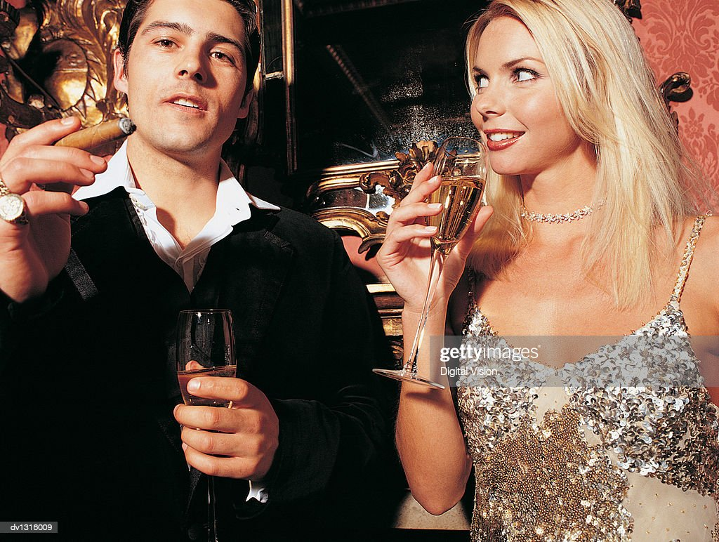 Couple Drinking Champagne And Smoking A Cigar Stock Photo