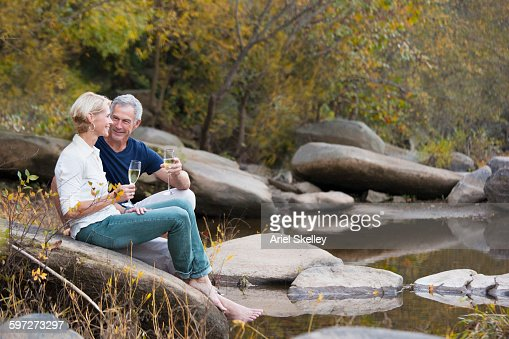 Couple drinking champagne at river