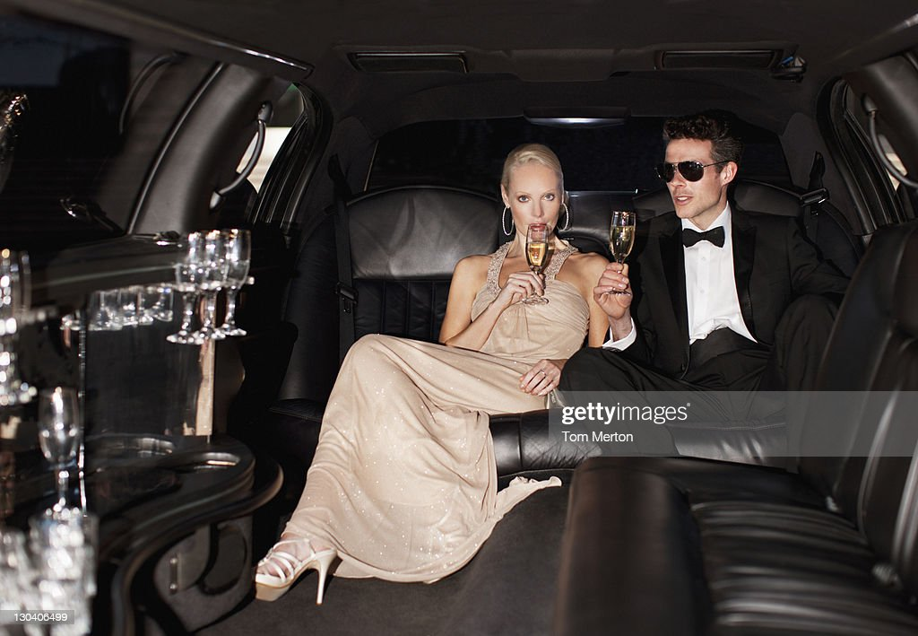 Couple drinking champagne in limo : Stock Photo
