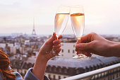 two glasses of champagne or wine, couple in Paris, romantic celebration of engagement or anniversary