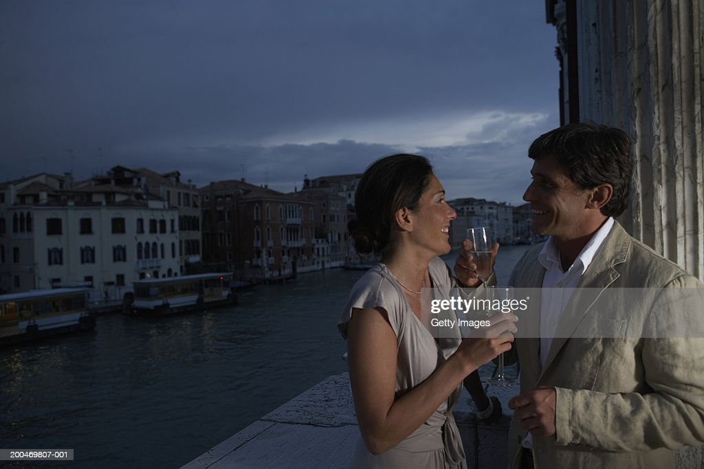 Couple drinking champagne on balcony, smiling at each other