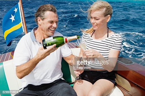 Couple drinking champagne on motorboat : Stockfoto