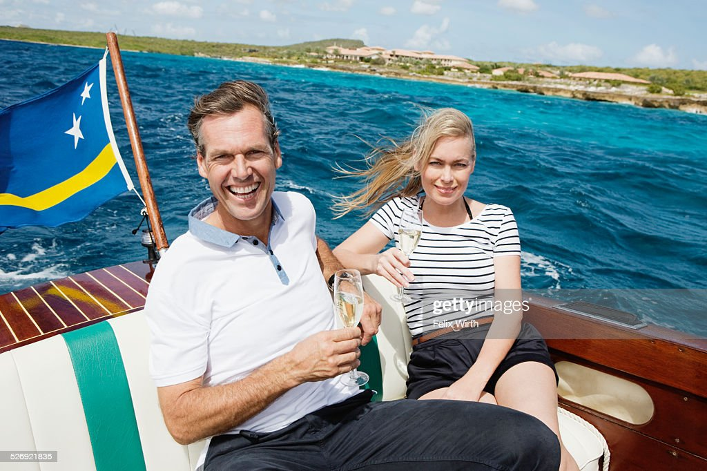 Couple drinking champagne on motorboat : Bildbanksbilder