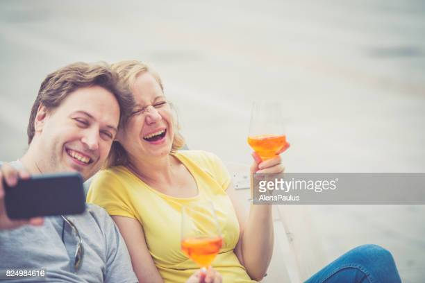 Couple drinking cocktail and taking photos outdoors