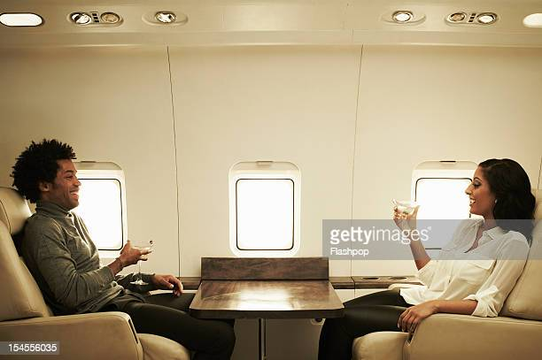 Couple drinking cocktails on private jet