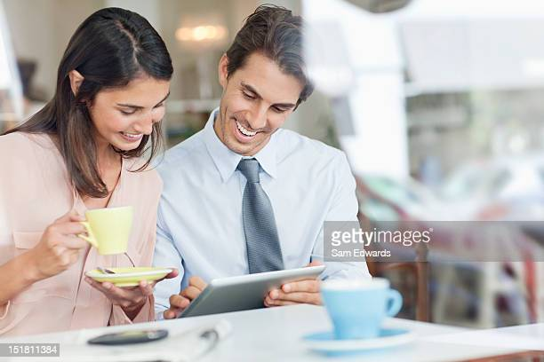 Couple drinking coffee and using digital tablet in cafe window