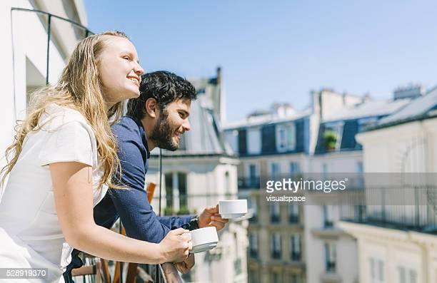 Pareja bebiendo café en la soleada balcón en algún lugar de Europa