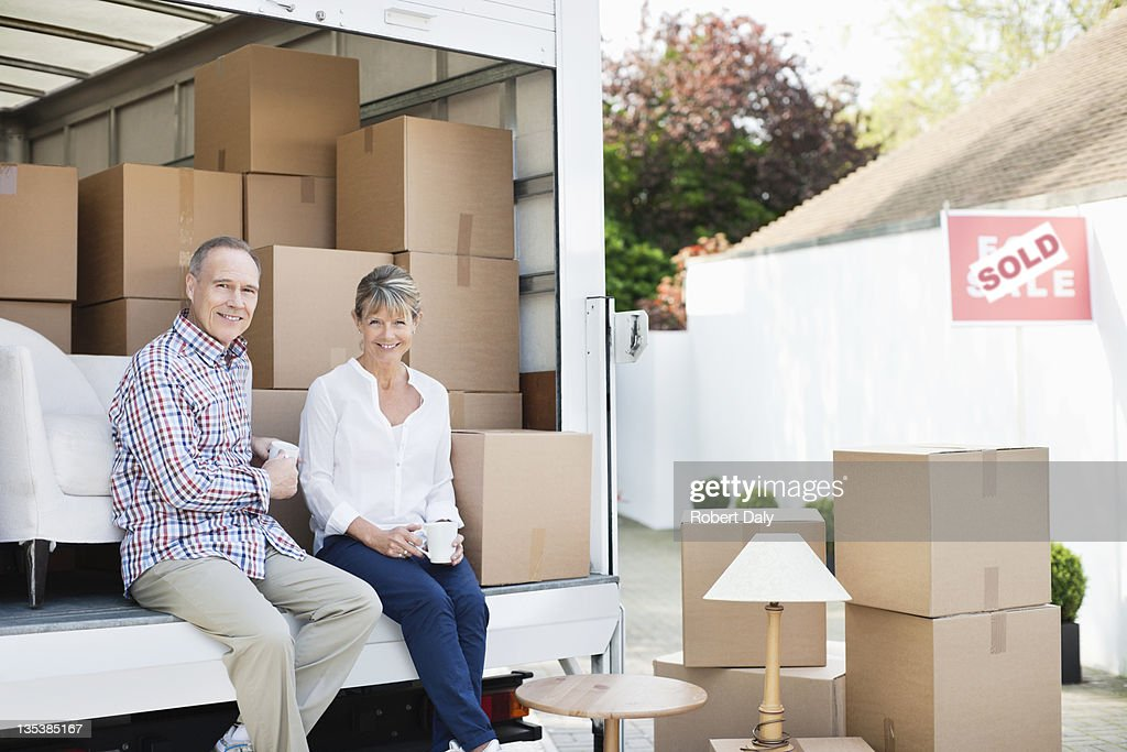 Couple drinking coffee on back of moving van : Stock Photo
