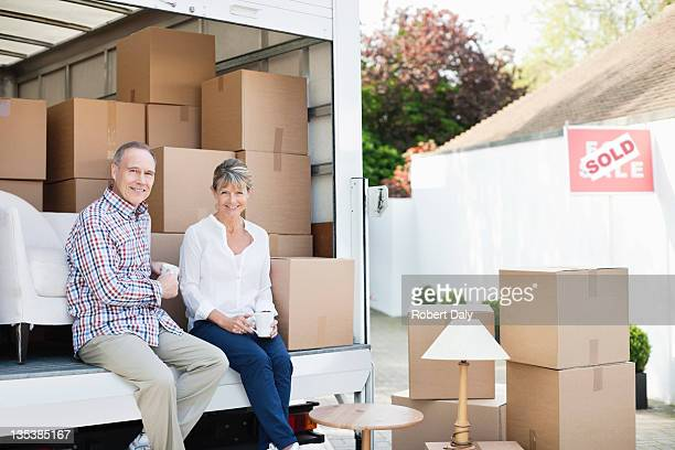 Couple drinking coffee on back of moving van