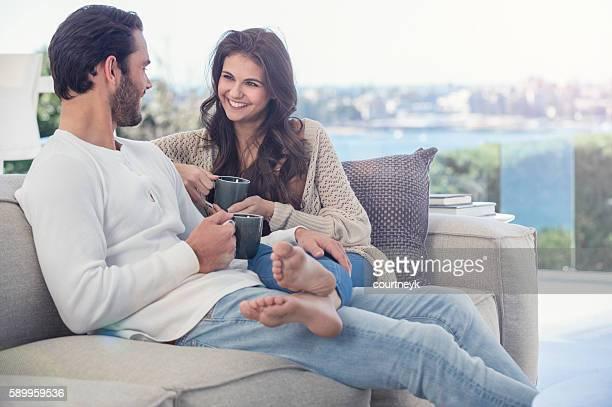 Couple drinking coffee on he sofa.