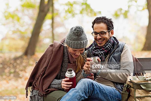 Couple drinking coffee on park bench