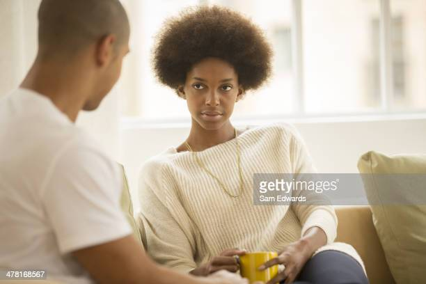 Couple drinking coffee on sofa