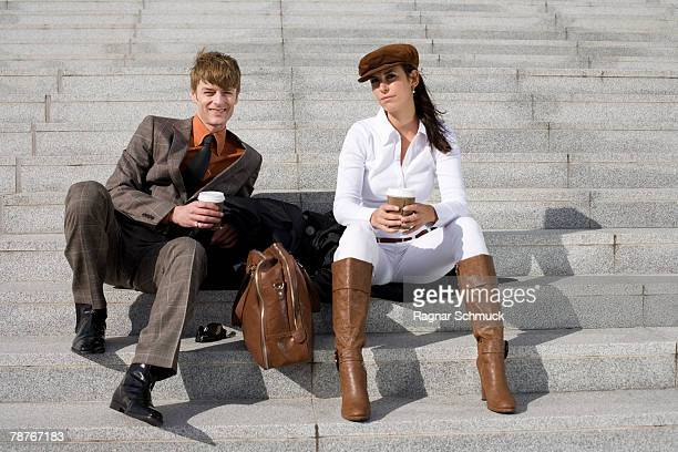 A couple drinking coffee on some steps