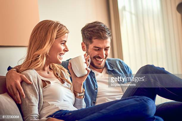 Couple drinking coffee on the sofa
