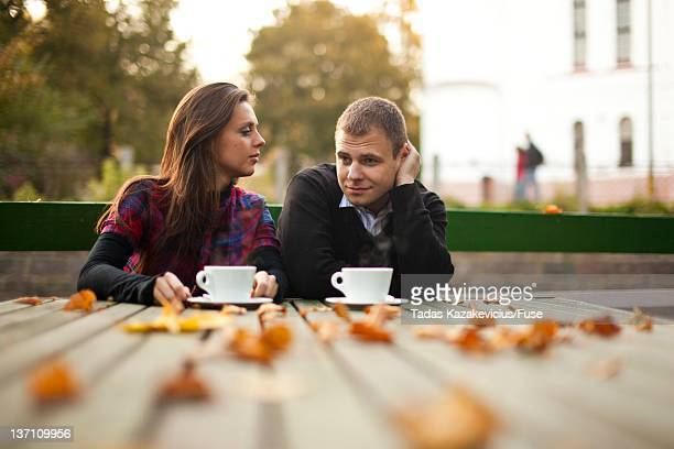 Couple drinking coffee outdoors in autumn scenery
