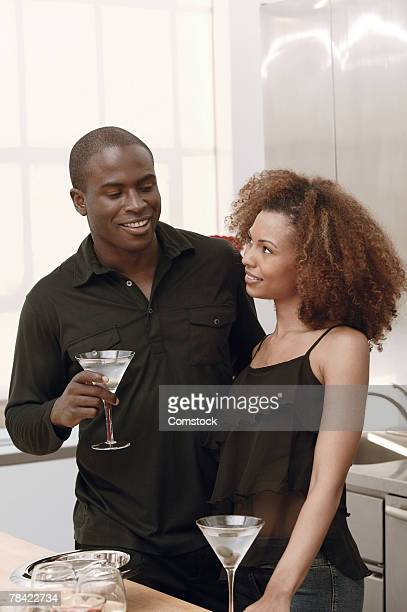 Couple drinking martinis in kitchen