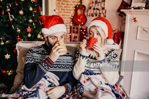 Couple drinking mulled wine by the fireplace, Christmas time