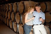 Couple drinking red wine in wine cellar