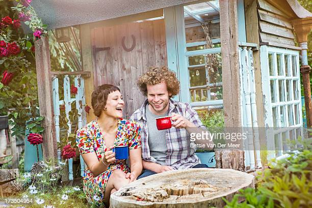 Couple drinking tea sitting in front of gardenshed