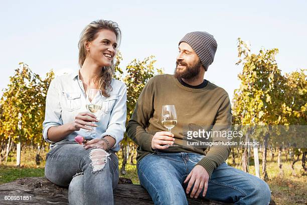 Couple drinking white wine on garden party in vineyard