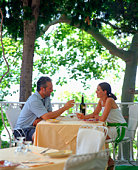 Couple drinking wine and sitting at outdoor dining table