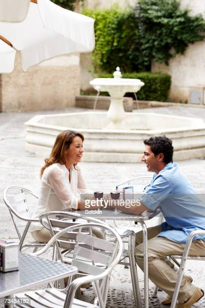 Couple drinking wine at outdoor restaurant with fountain, high angle view