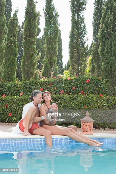 Couple drinking wine by pool
